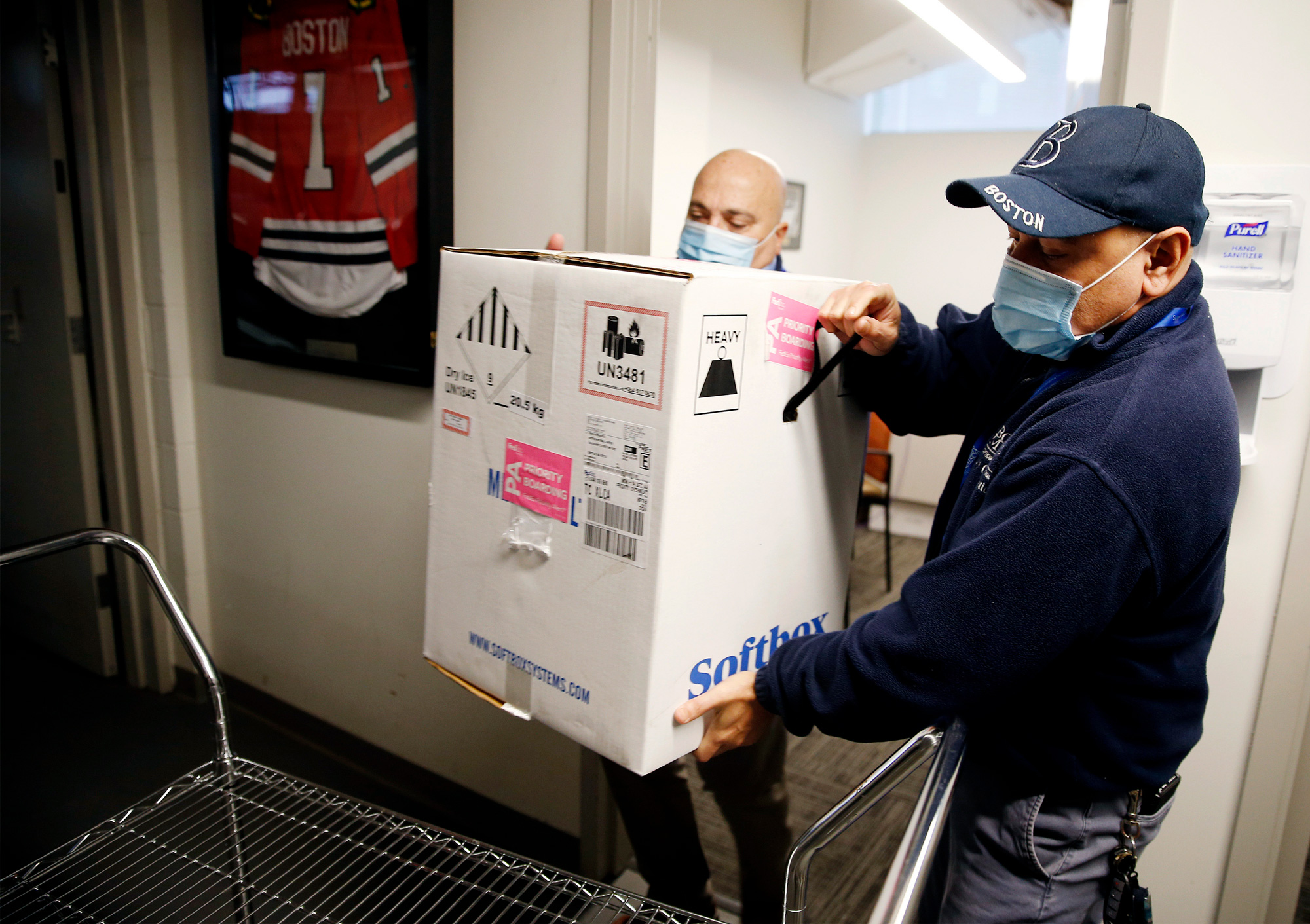 Victor Ruiz with Boston Medical Center Supply Chain Operations and Richard Guarino, left, BMC Supply Chain Operations Associate Director place the hospital's first shipment of the Pfizer-BioNTech COVID-19 vaccine on a cart to deliver to the pharmacy at Boston Medical Center on December 14 in Boston.
