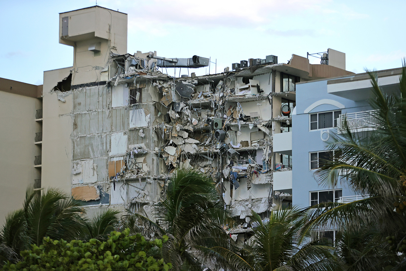 Debris dangles from Champlain Towers South Condo after the multistory building partially collapsed on Thursday, June 24, in Surfside, Florida.