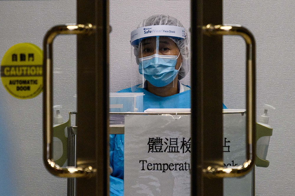 A medical worker wearing protective gear waits to take the temperature of people entering Princess Margaret Hospital in Hong Kong on February 4