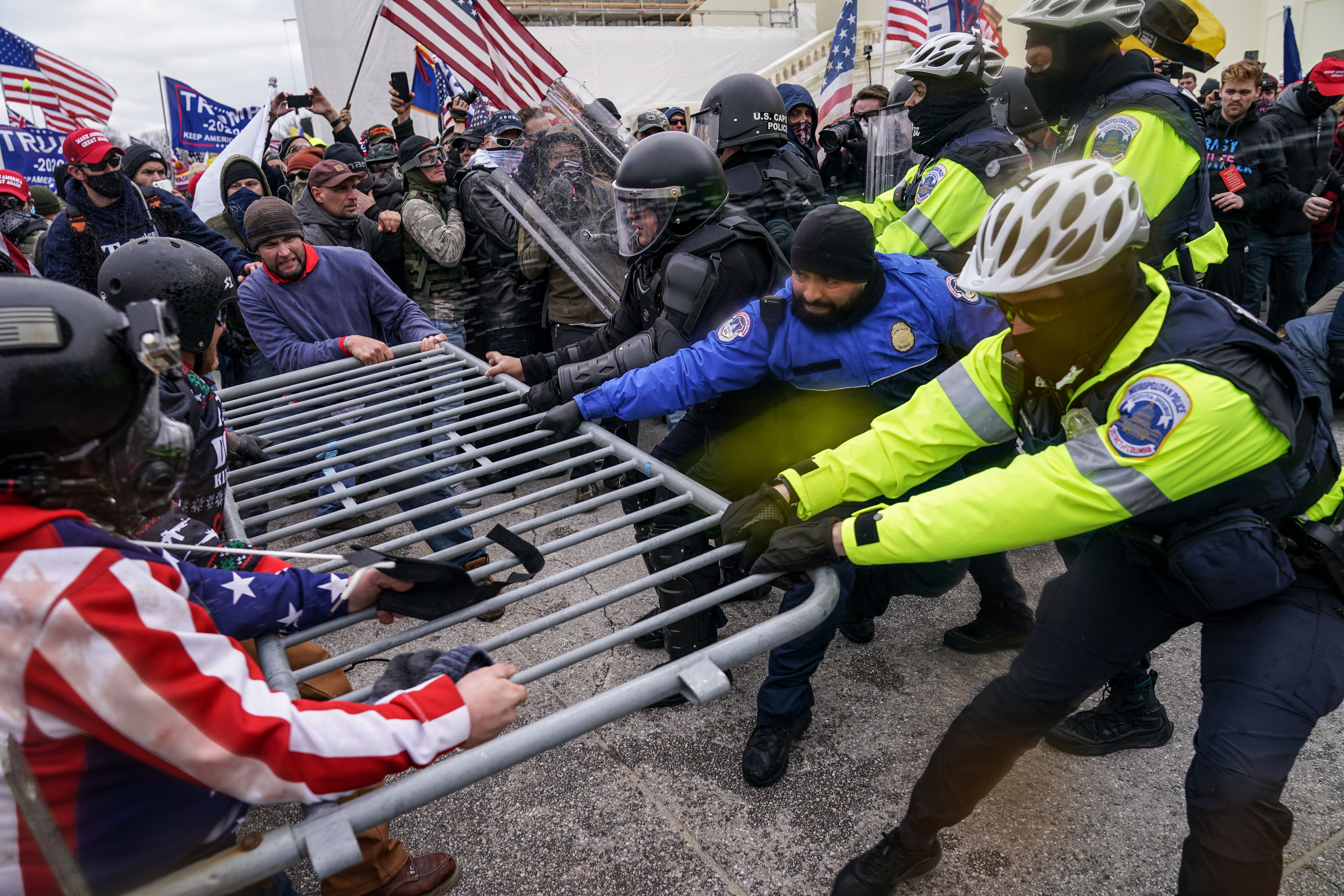 Pro-Donald Trump rioters try to break through a police barrier on January 6 at the Capitol.