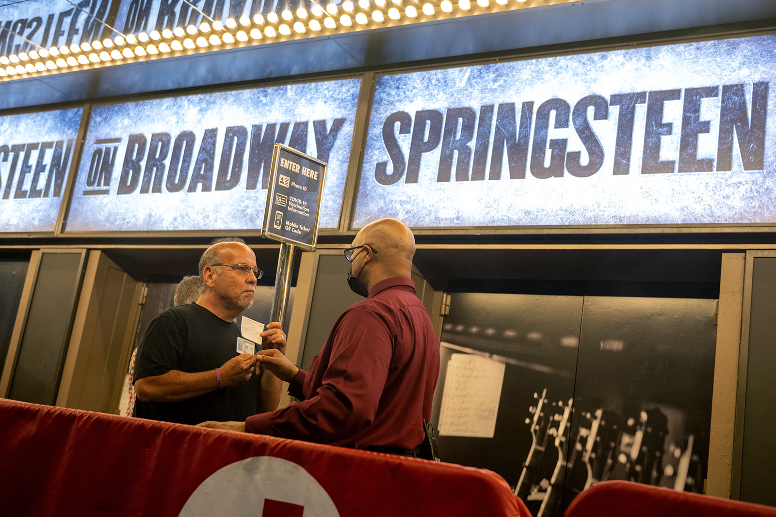 """A person without a mask shows their Covid-19 vaccination card before entering """"Springsteen on Broadway"""" at the St. James Theatre in Times Square on July 10, in New York City."""