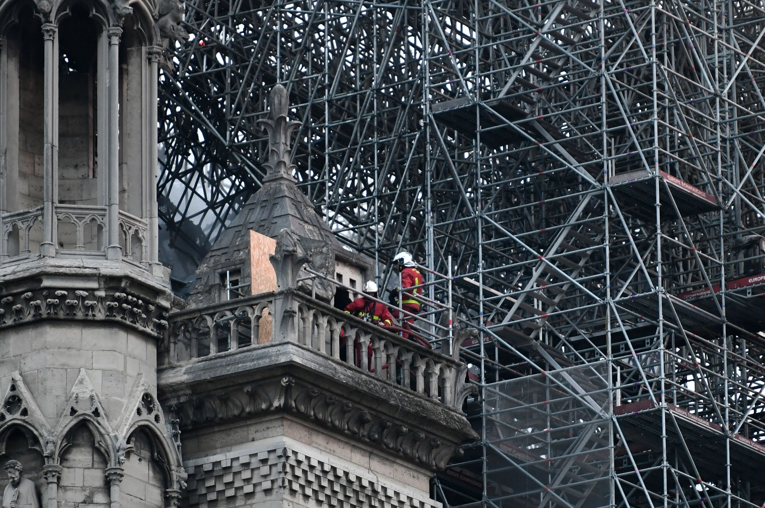 """Firefighters continue to work to extinguish the fire at Notre Dame Cathedral. The fire is under control but there are """"still outbreaks,"""" a Ministry of the Interior spokesman said Tuesday morning."""
