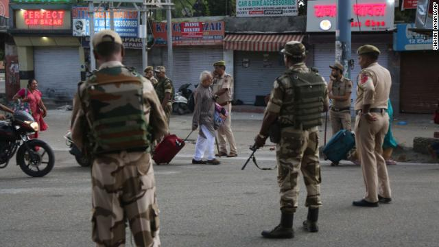 Tourists walk past Indian security forces during curfew-like restrictions in Jammu, India on Monday.