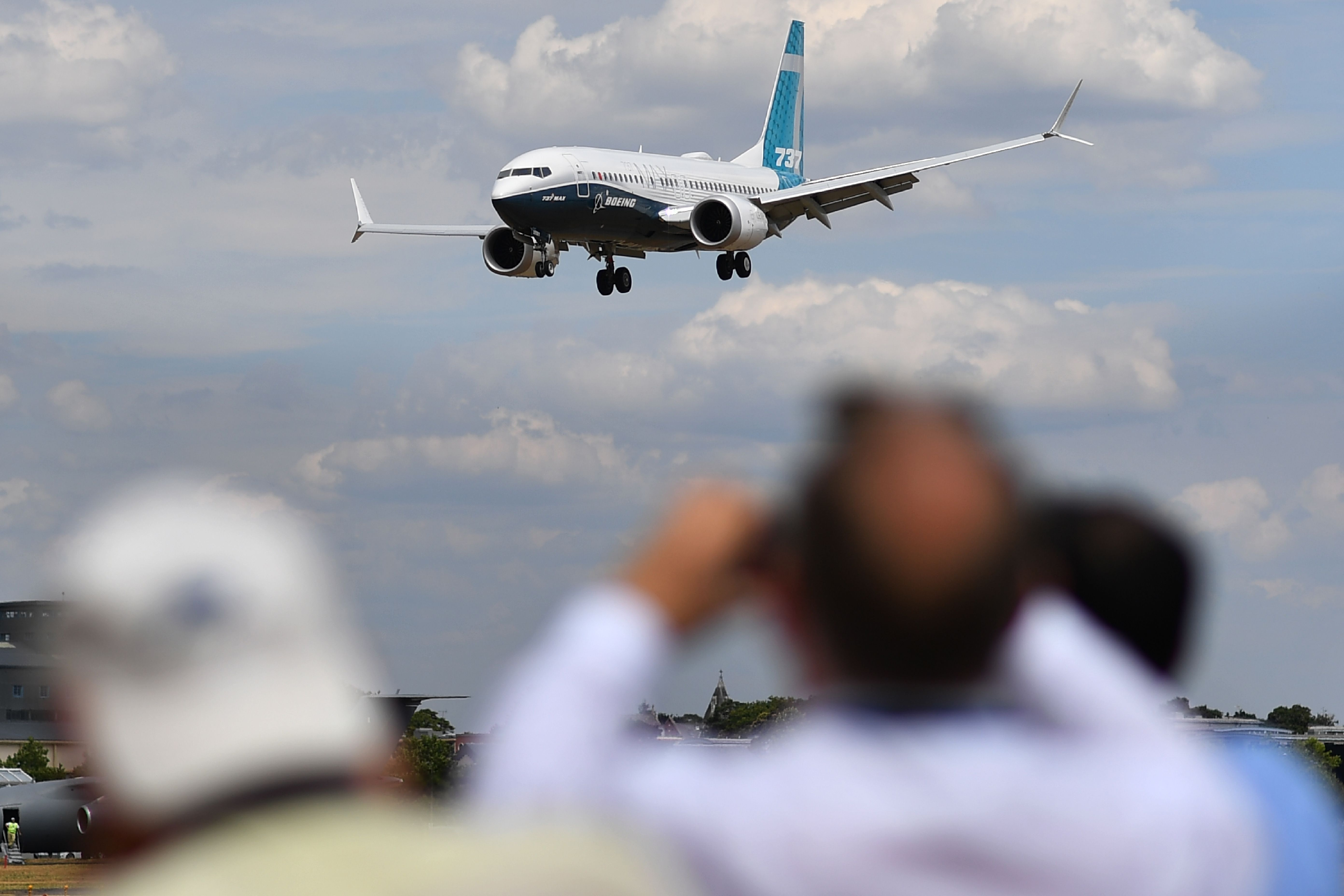 Visitors watch as a Boeing 737 Max lands after an air display during the Farnborough Airshow, south west of London, in July 2018.