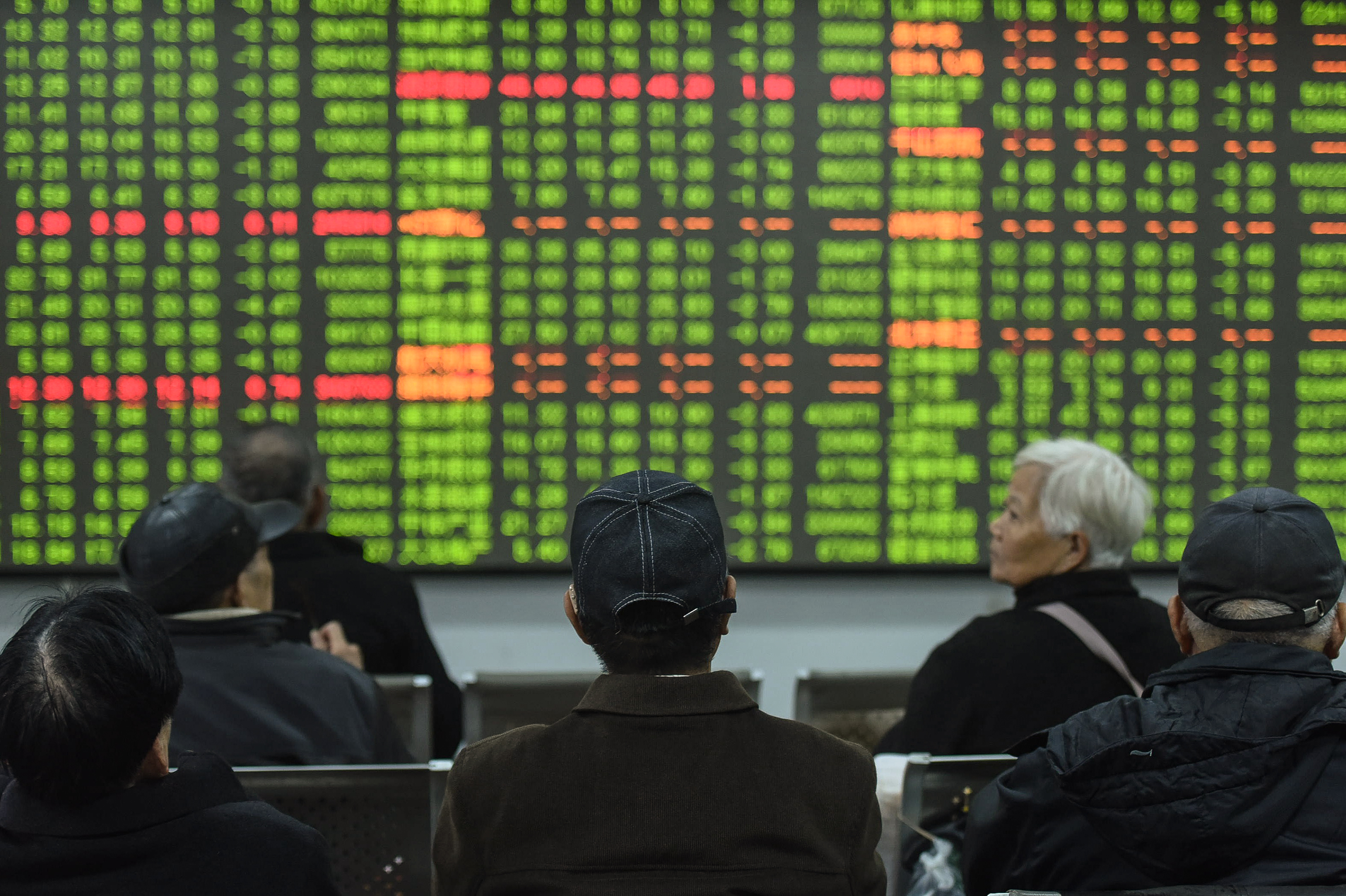 Investors look at a screen showing stock market movements in Hangzhou, China, on February 3, 2020.