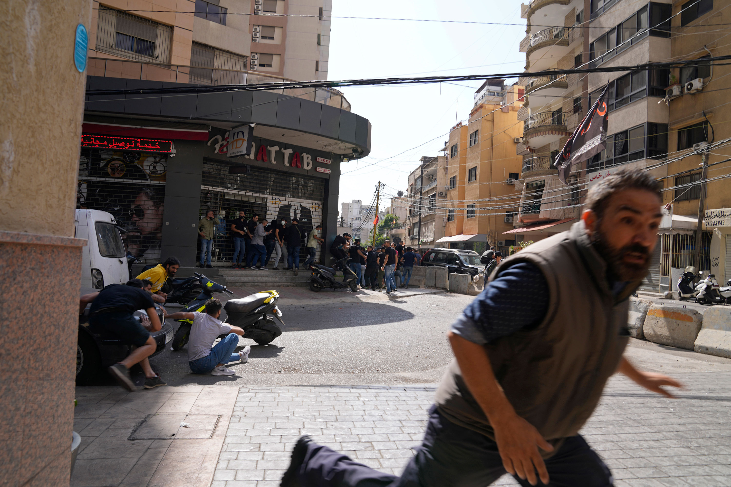A man runs for cover as gunfire erupts in Beirut on October 14.