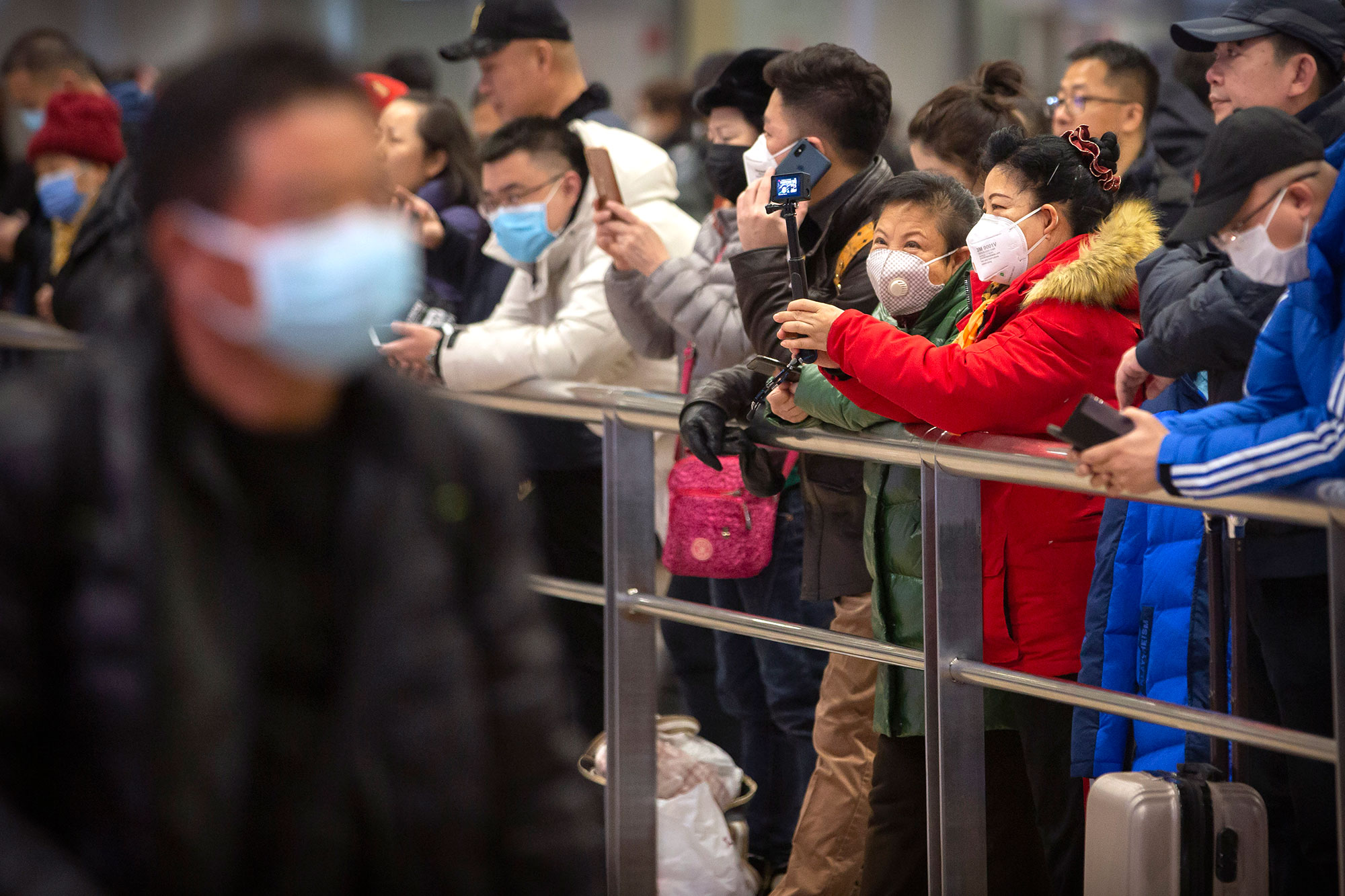 People wear face masks as they wait for arriving passengers at Beijing Capital International Airport in Beijing on January 23.