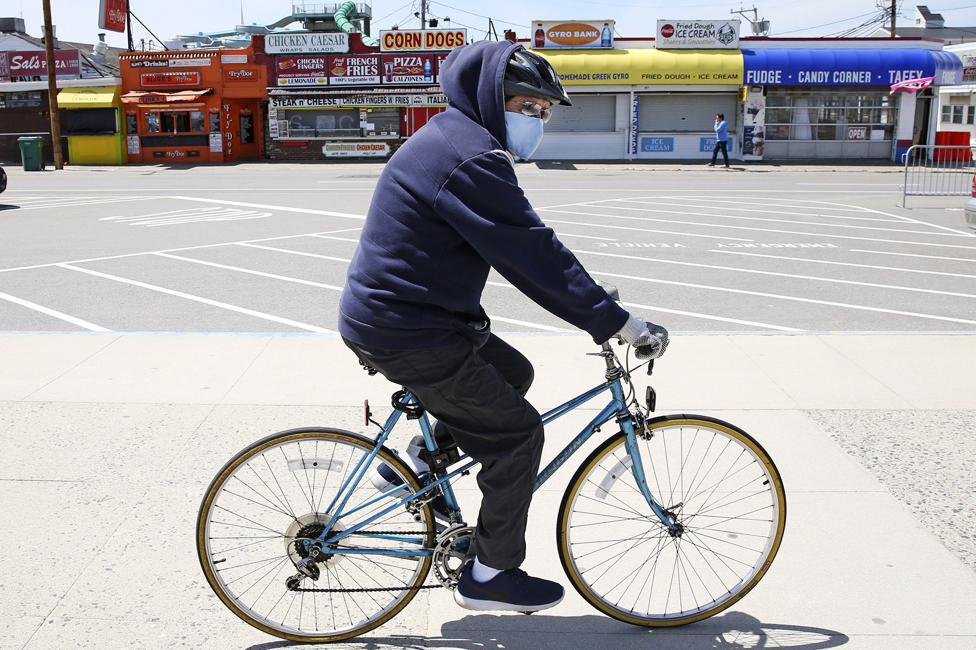A man wearing a protective mask and gloves cycles past the Boardwalk across from the Hampton Beach State Park in Hampton, New Hampshire, on Tuesday, May 19.