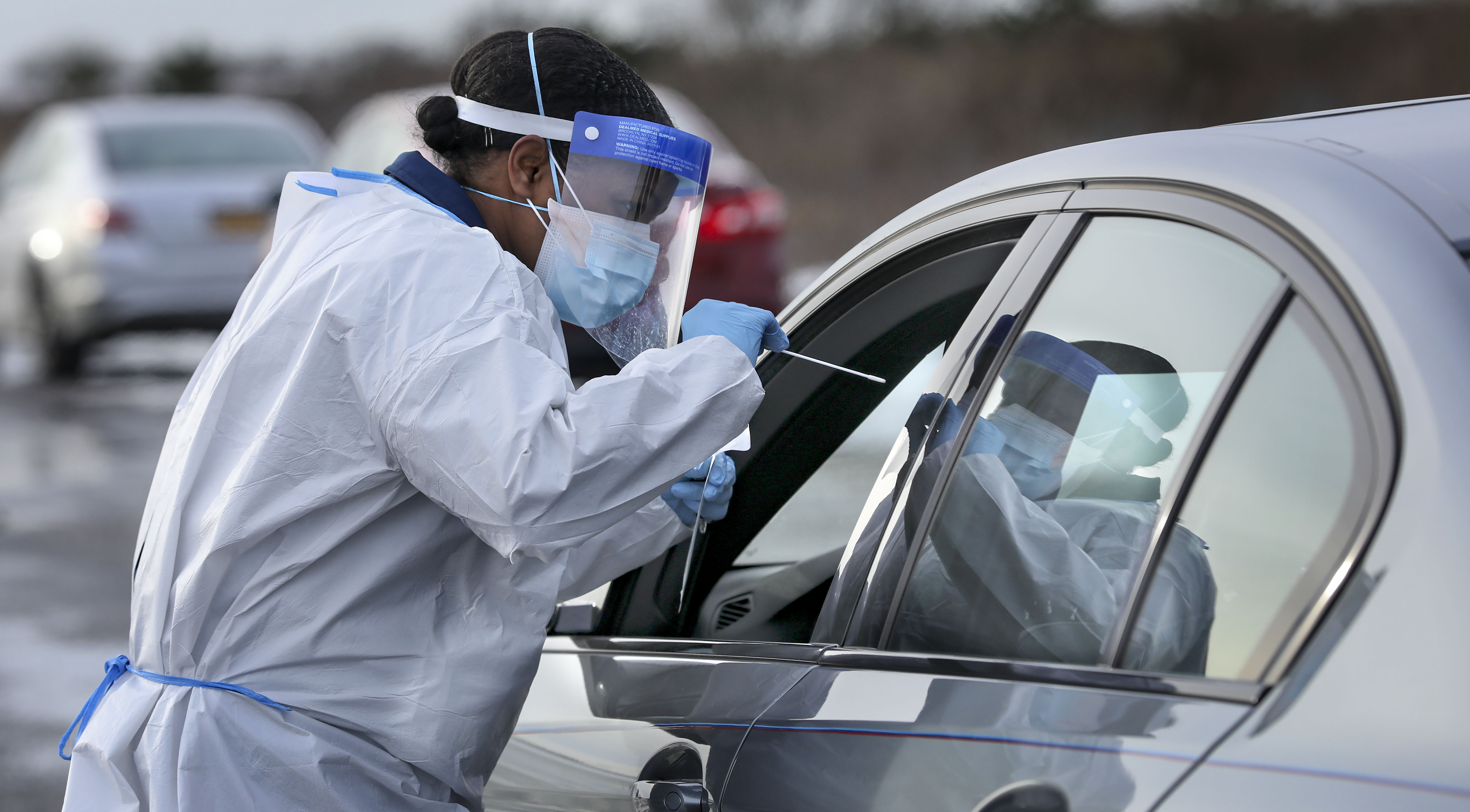 A nurse practitioner administers a Covid-19 swab test at a drive-thru testing site in Shirley, New York, on December 18, 2020.