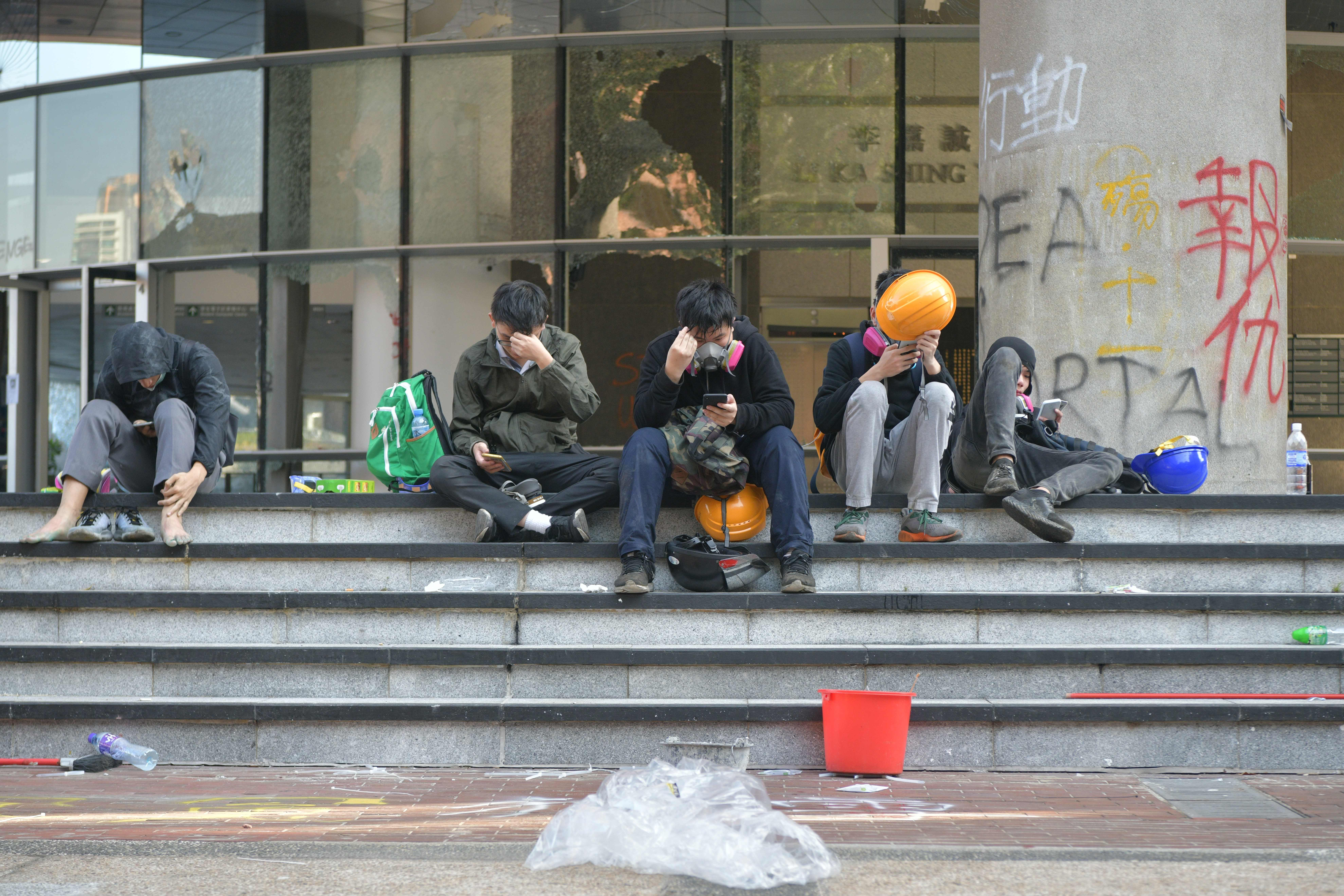 A group of protesters rest on stairs after unable to find safe passage out of Hong Kong Polytechnic University in Hung Hom district of Hong Kong on November 18.