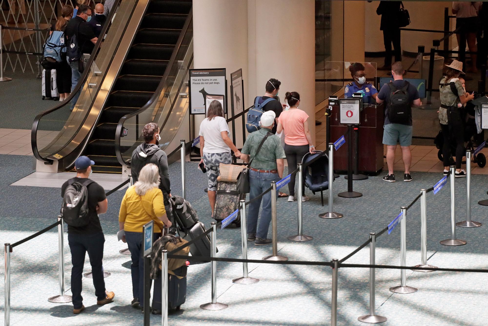 Passengers line up to enter TSA pre-check at Orlando International Airport on June 17 in Orlando.