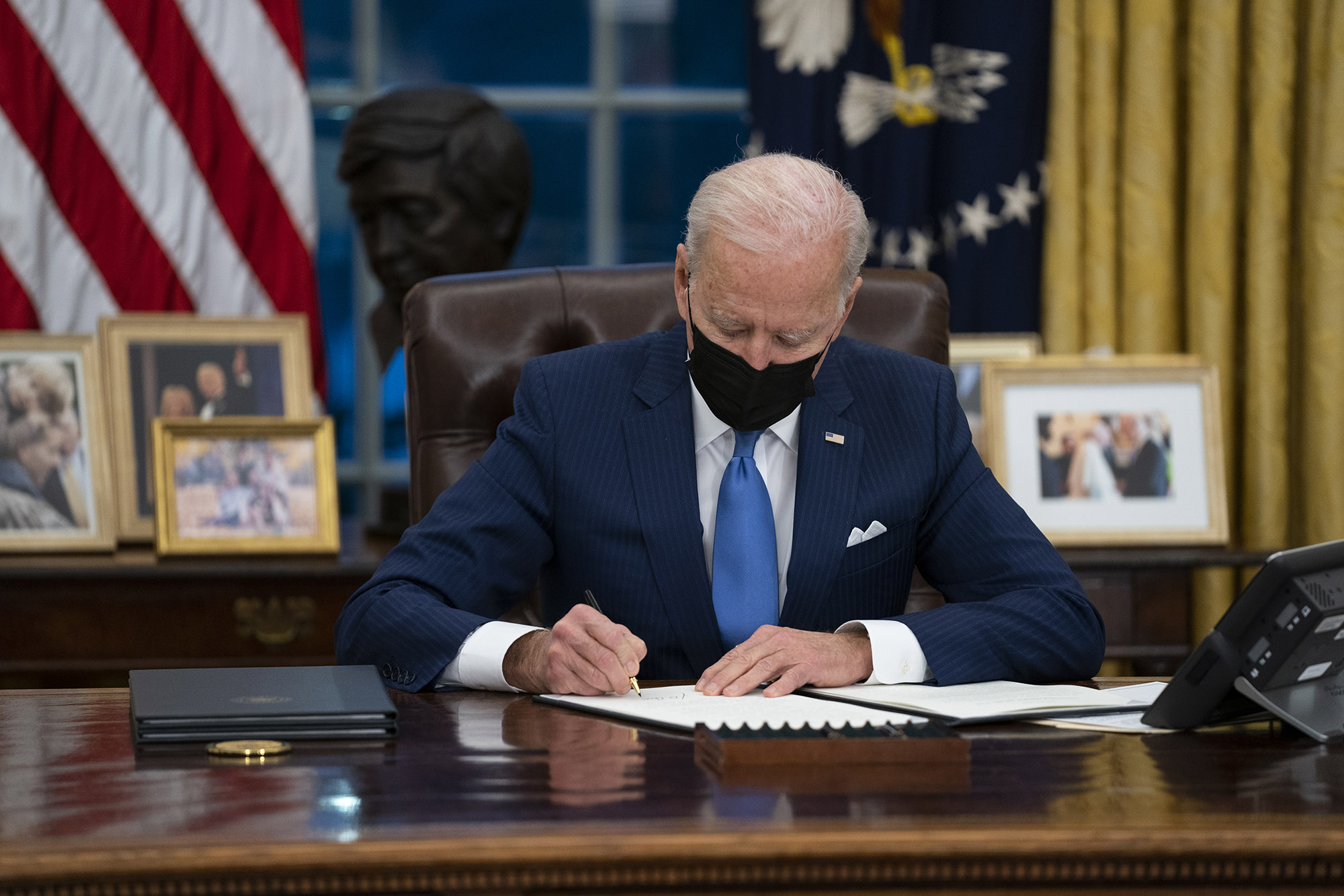 President Joe Biden signs an executive order on immigration, in the Oval Office of the White House on Tuesday, February 2, in Washington, DC.