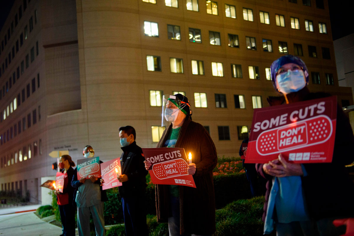 Nurses hold candles during a vigil organized by California Nurses United for healthcare workers who died from Covid-19 in Los Angeles, California on November 23.