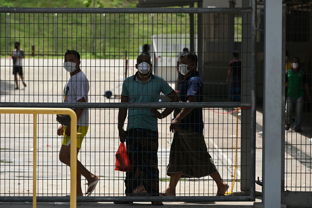 Foreign workers, wearing face masks as a preventive measure against the spread of the coronavirus, look out from the fence of the workers' dormitory in Singapore on April 9.