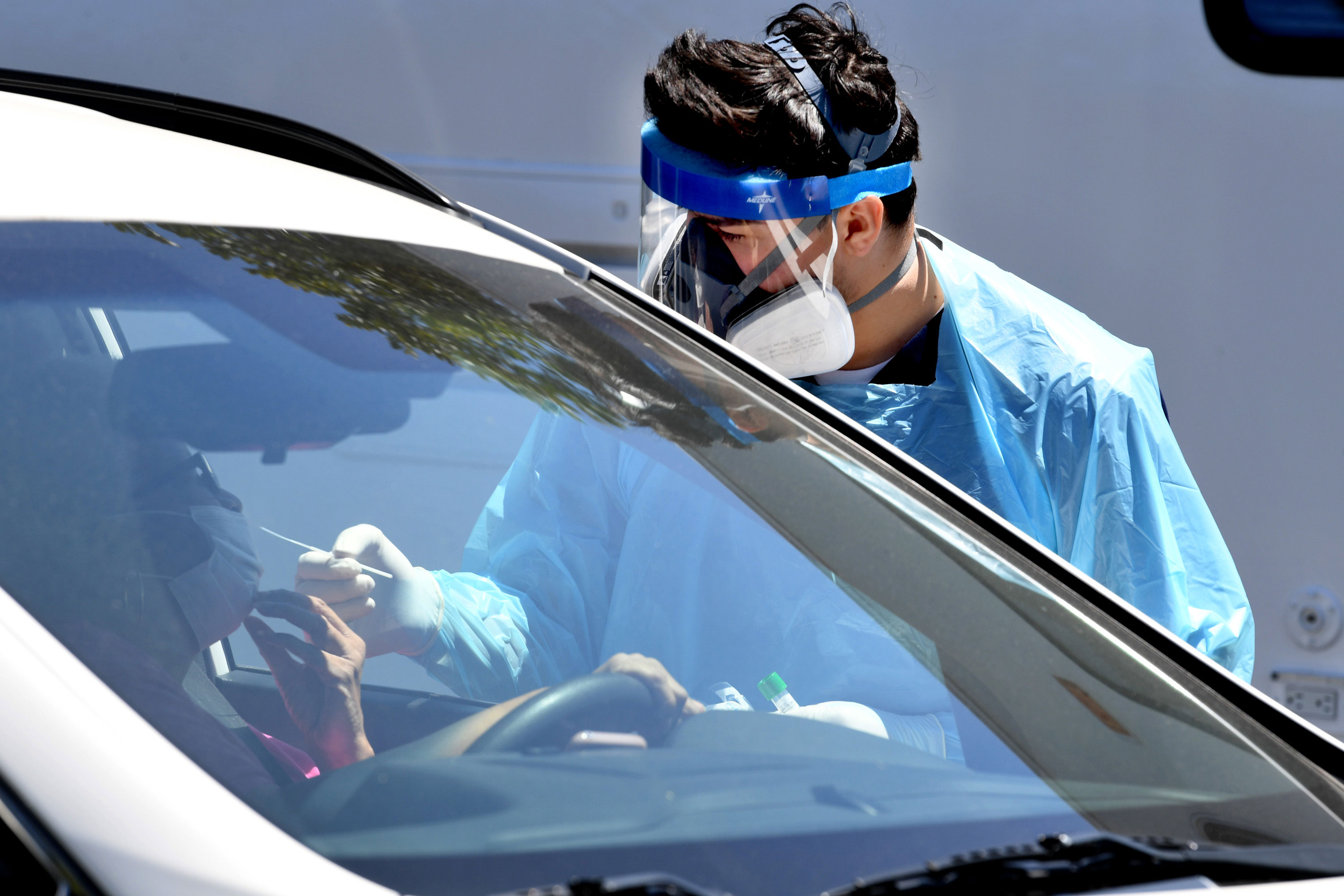 A worker administers a coronavirus test swab at a drive-thru testing site on April 24 in Los Angeles, California.