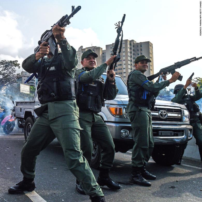 Members of the Bolivarian National Guard who joined Venezuelan opposition leader and self-proclaimed acting president Juan Guaido fire into the air to repel forces loyal to President Nicolas Maduro who arrived to disperse a demonstration near La Carlota military base in Caracas.