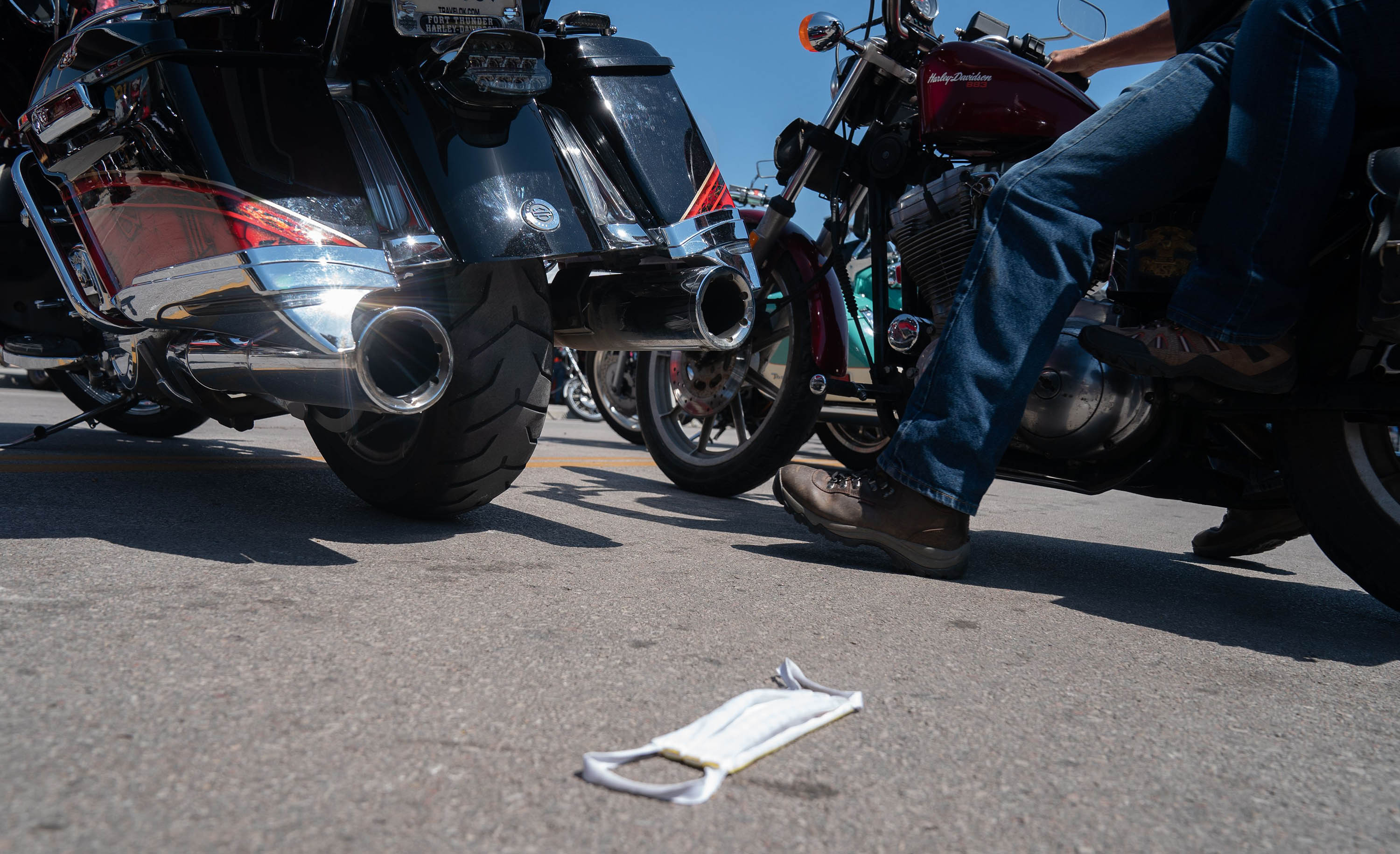 A man rides past a discarded face mask during the 80th Annual Sturgis Motorcycle Rally on August 8 in Sturgis, South Dakota.