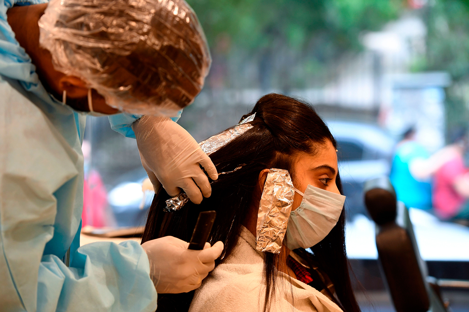 A hairdresser wearing personal protective equipment works on a customer at a hair salon in New Delhi on June 9.