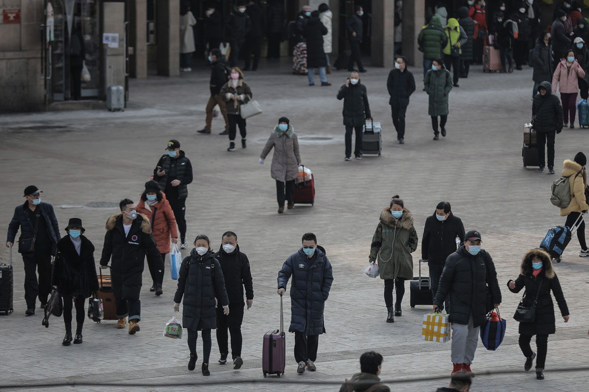 People wearing protective face masks are seen at the Beijing Railway Station on January 19, ahead of the Chinese New Year travel rush.