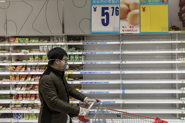 A customer pushes a cart past empty egg shelves at a supermarket in Shanghai, China, on Tuesday, January 28.