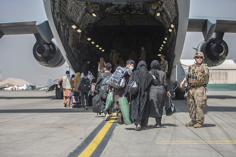 In this image provided by the U.S. Marine Corps, families begin to board a U.S. Air Force Boeing C-17 Globemaster III during an evacuation at Hamid Karzai International Airport in Kabul, Afghanistan, Monday, August 23.