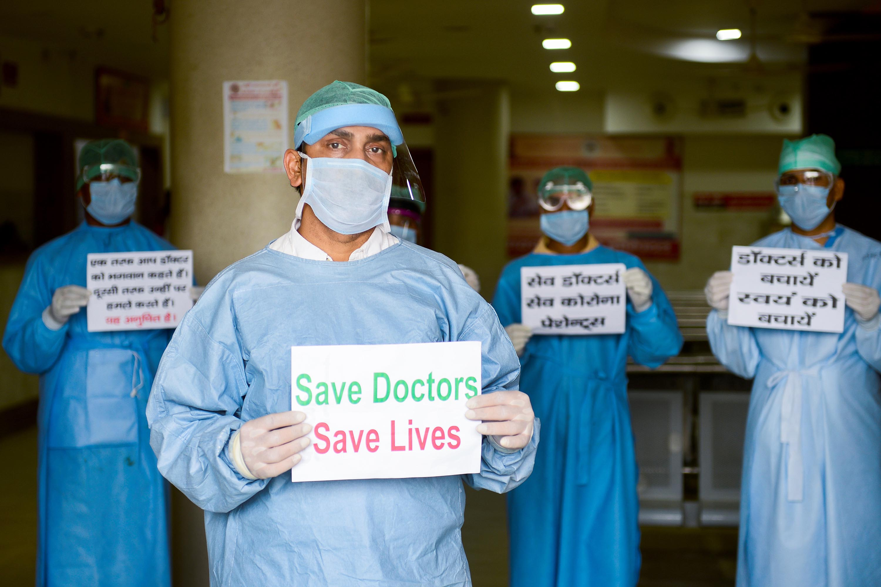 Doctors and medical staff of Narayan Swaroop Hospital in Allahabad hold placards to protest against recent assaults on health workers in India, on April 16.