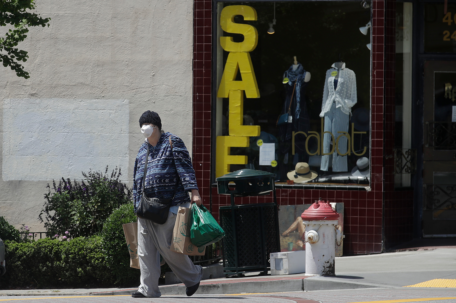 A woman carries shopping bags during the coronavirus outbreak in San Francisco, on Thursday, May 7.