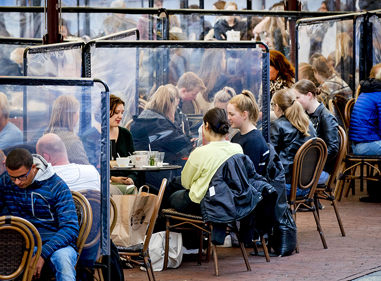 People sit at terraces with plastic screens in Groningen, The Netherlands, on September 25, 2020.