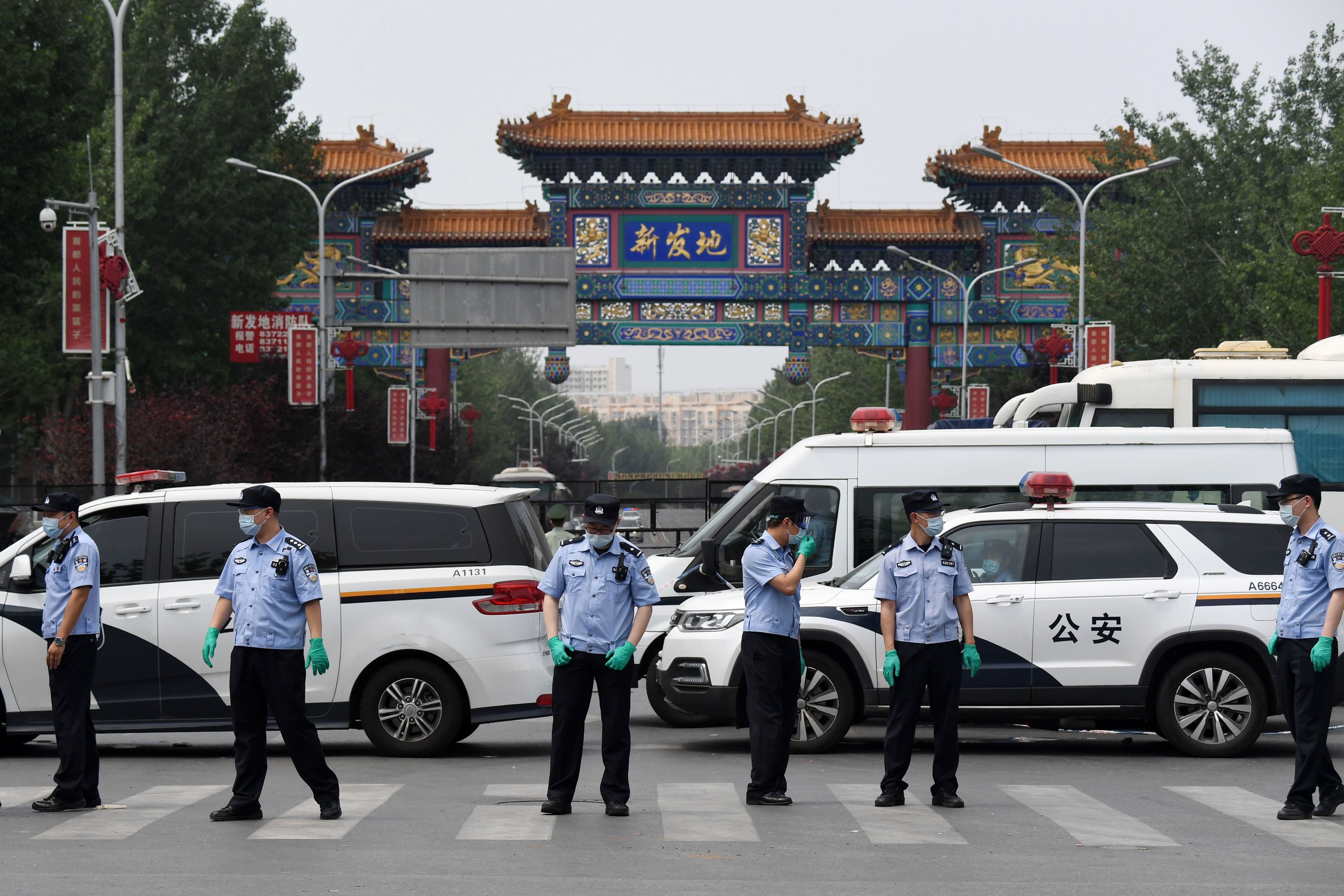 Police guard the entrance to the closed Xinfadi market in Beijing on June 13.