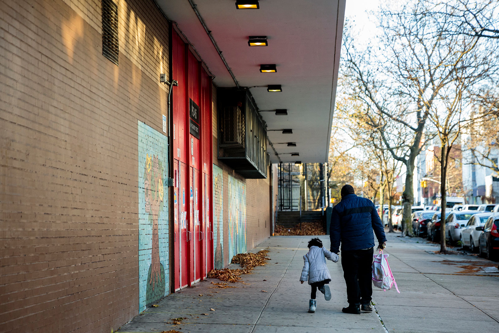 A parent walks their child to school in New York on November 16. New York City public schools grades 3-k, Pre-k, and K-5th grade will begin reopening for in-person learning Dec. 7, Mayor Bill de Blasio said.