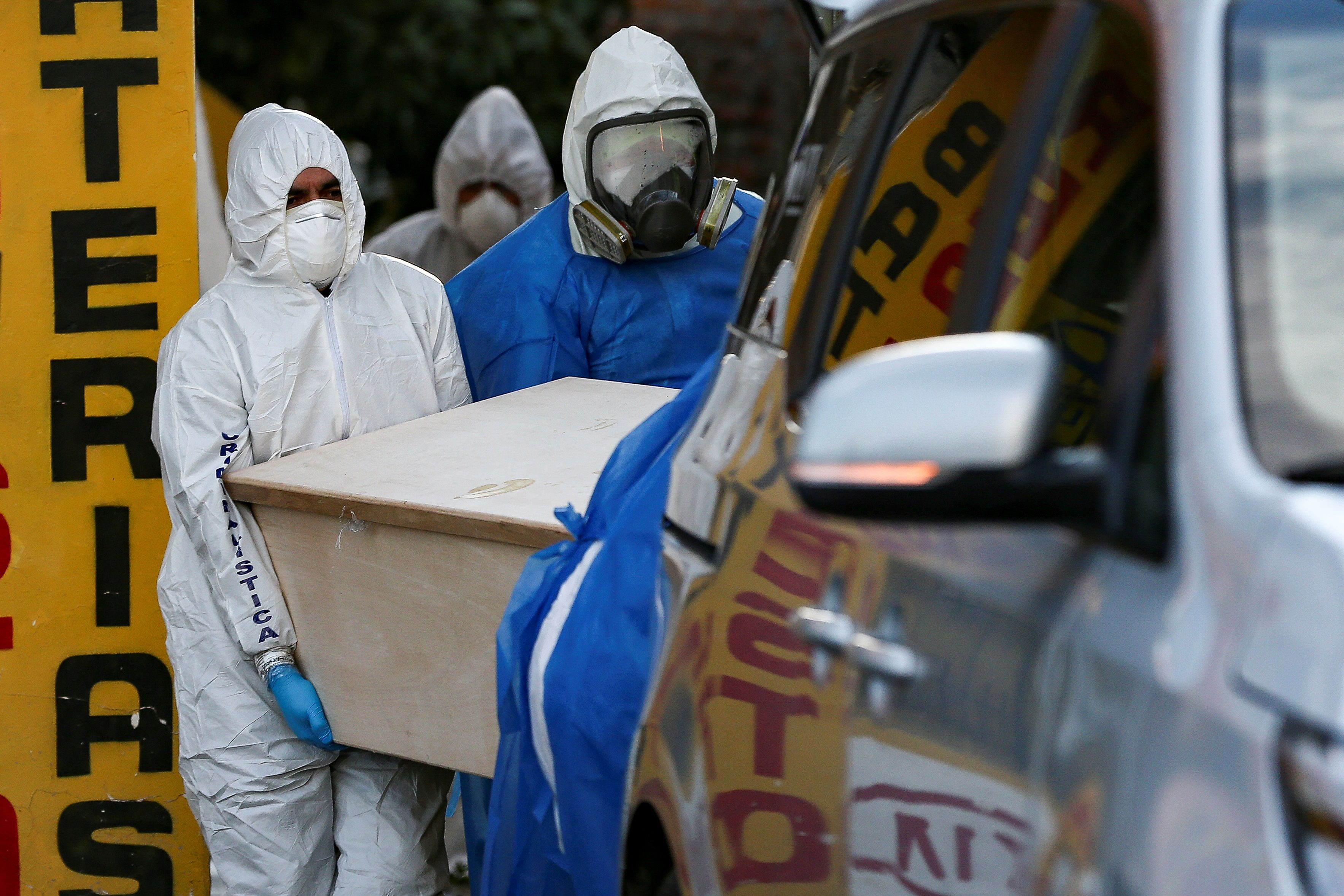 Police and funeral staff remove the body of a person said to have died from Covid-19 in a peripheral neighborhood of Quito, Ecuador, on May 7.