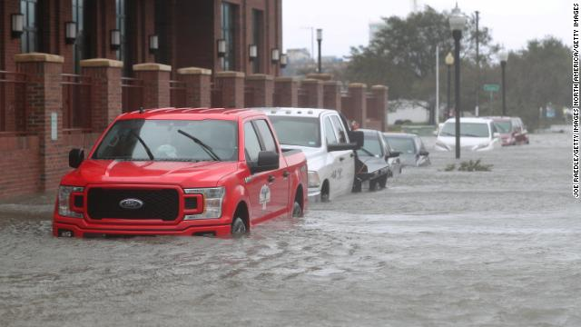 Vehicles parked on a flooded street as Sally passes through Pensacola, Florida, on Sept. 16.