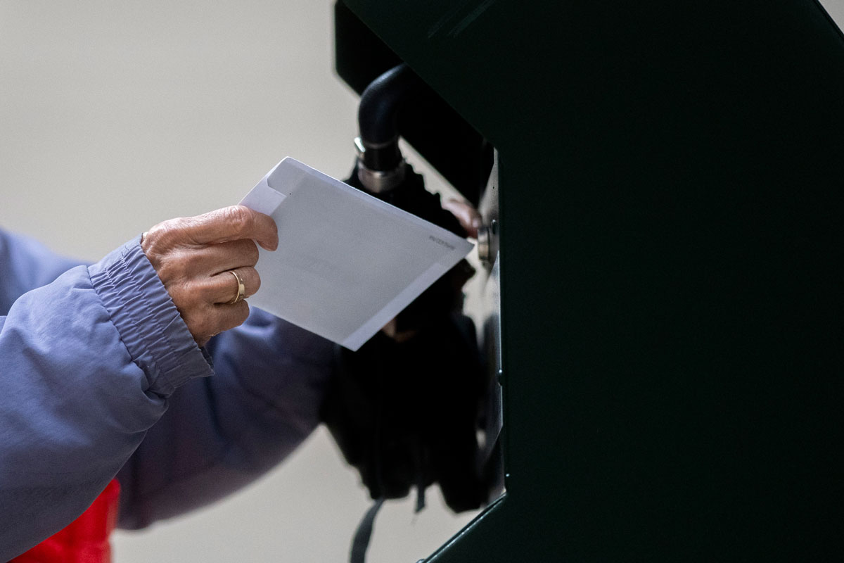 A voter deposits their ballot into an official ballot drop box in Philadelphia, Pennsylvania on October 27.