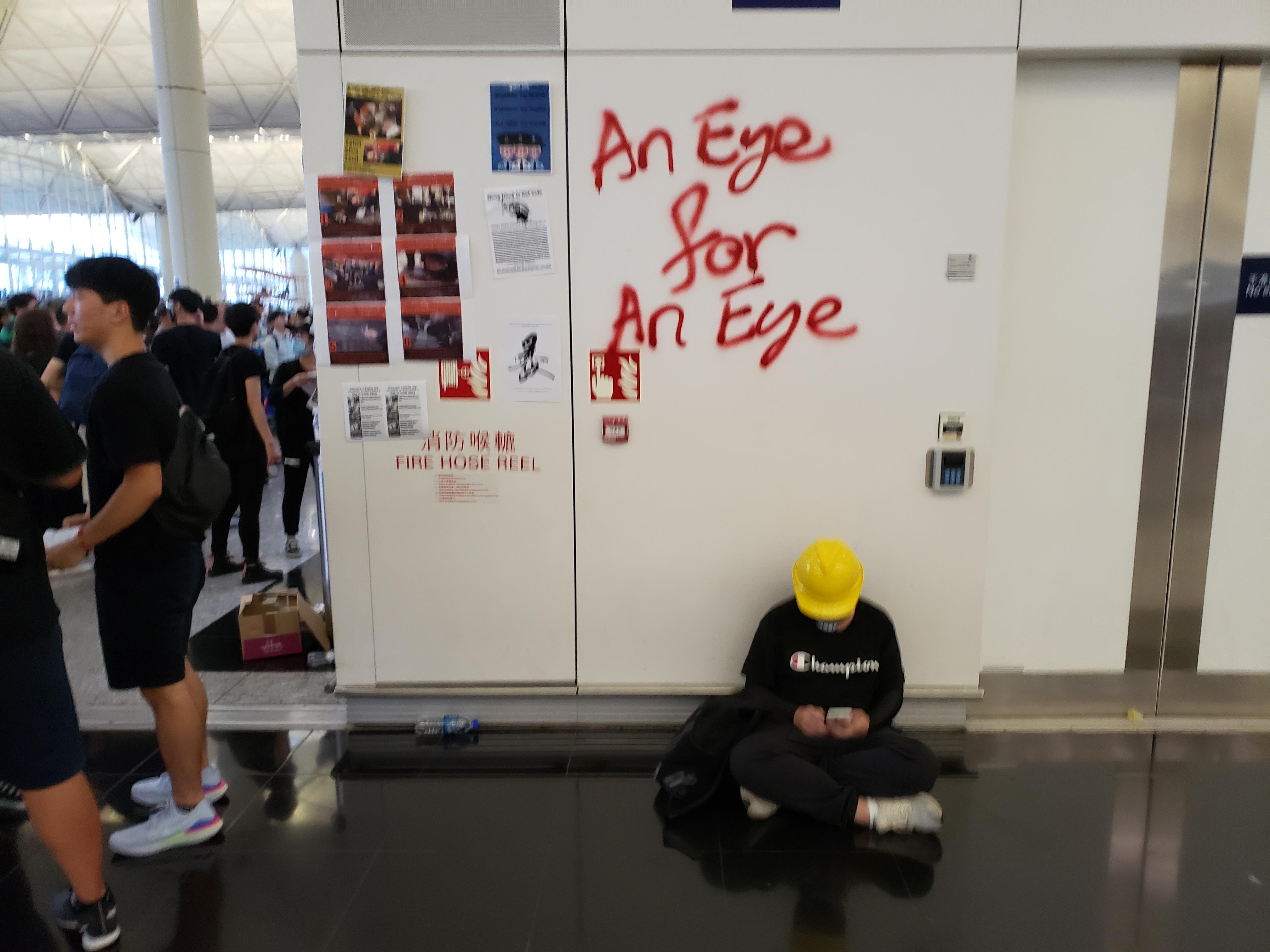 A protester takes a break under graffiti at Hong Kong airport on Monday night.