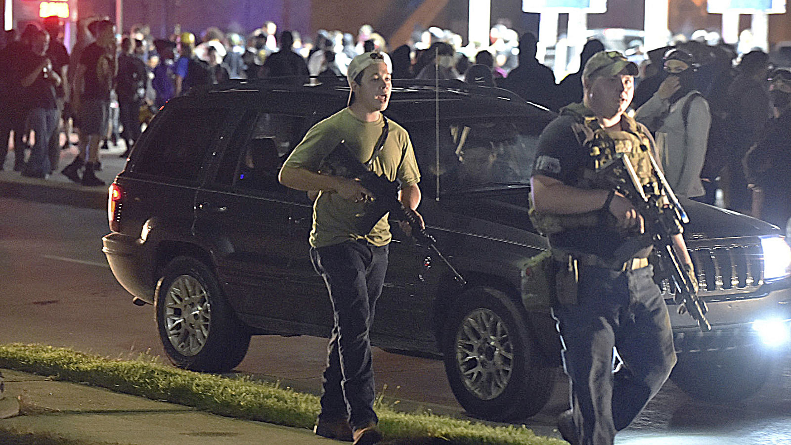 Kyle Rittenhouse, left with backwards cap, walks along Sheridan Road in Kenosha, Wisconsin, on Tuesday, August 25, with another armed civilian.