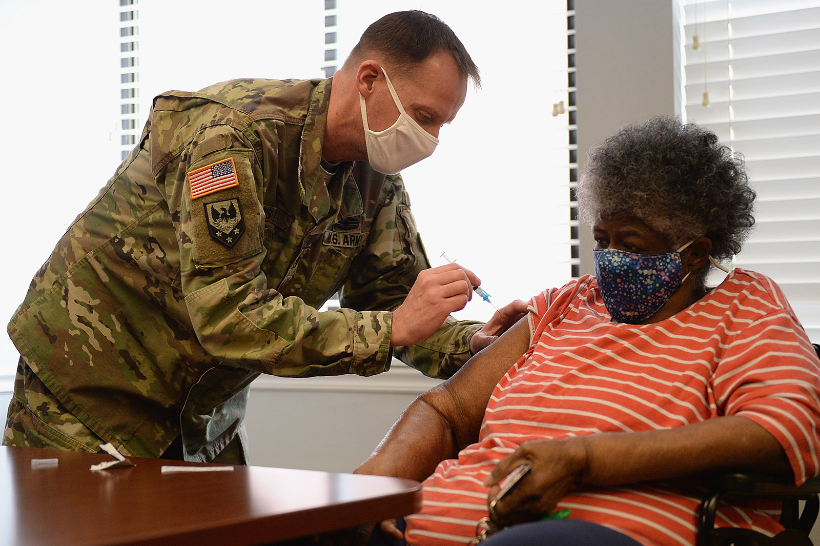 Staff Sgt. Herbert Lins of the Missouri Army National Guard administers the Covid-19 vaccine to a resident during a vaccination event on February 11 at the Jeff Vander Lou senior living facility in St. Louis, Missouri.