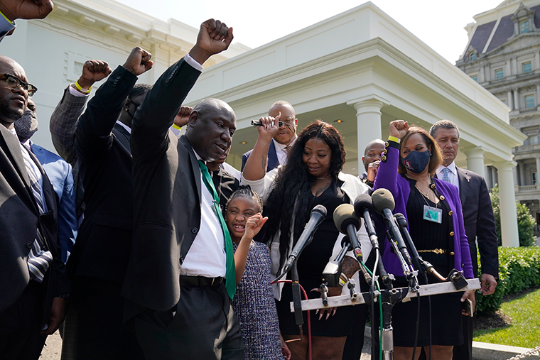 Benjamin Crump, front center, along with Gianna Floyd, daughter of George Floyd, and her mother Roxie Washington, and others talk with reporters after meeting with President Joe Biden at the White House, Tuesday, May 25.