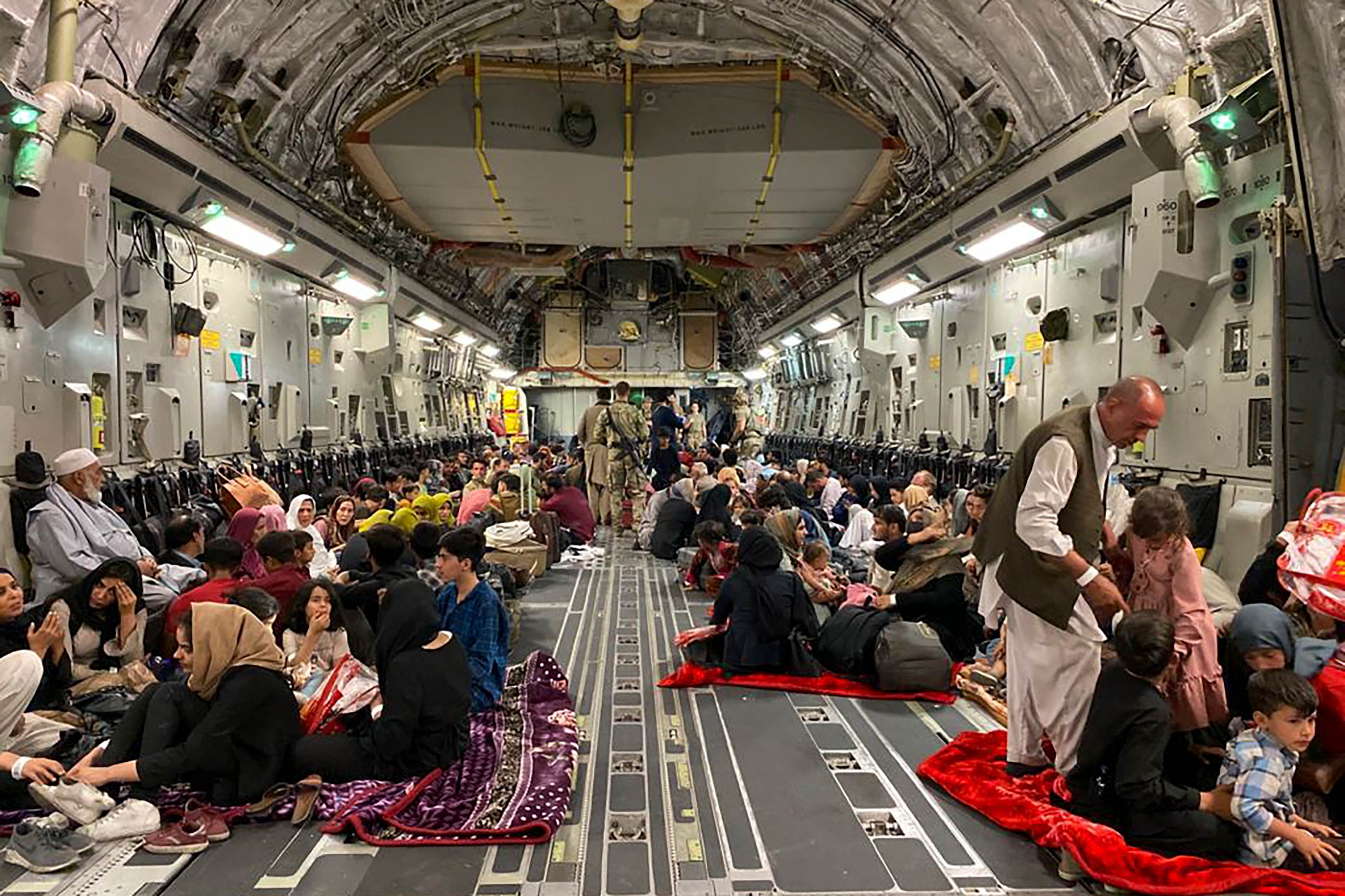 People sit inside a US military aircraft to leave Afghanistan at the airport in Kabul on August 19.