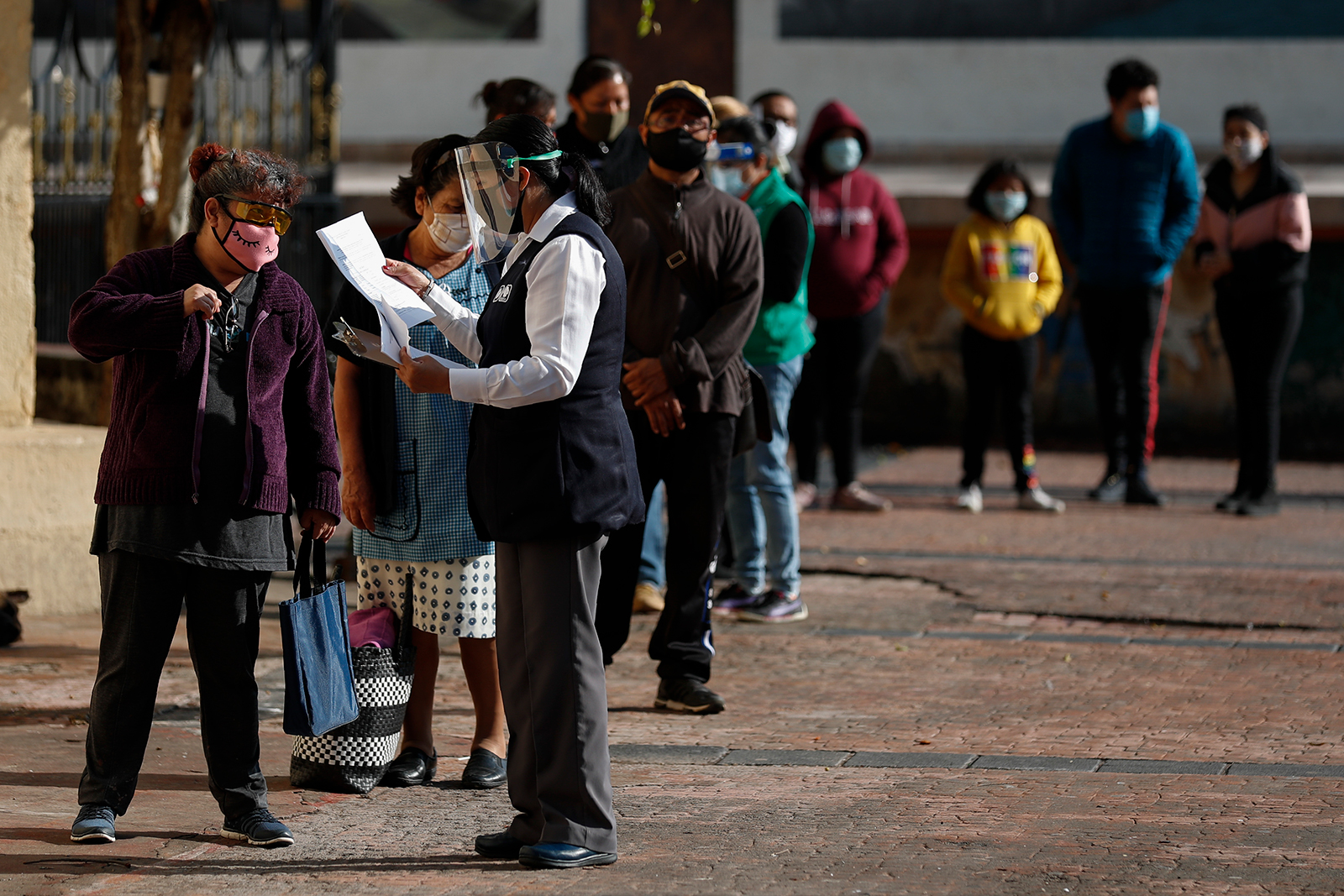 A health department worker collects patient data from people waiting in line for Covid-19 testing, at a mobile diagnostic tent in Mexico City on July 24.