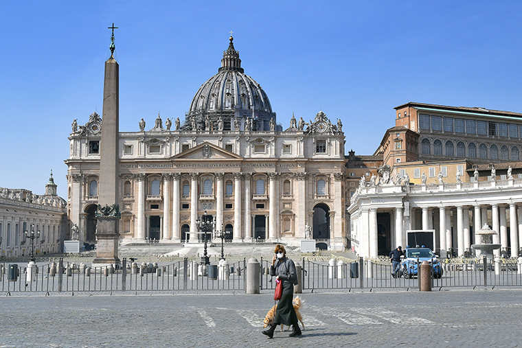 A woman,walks past the empty Saint Peter's square on Sunday, March 22, 2020 at the Vatican.