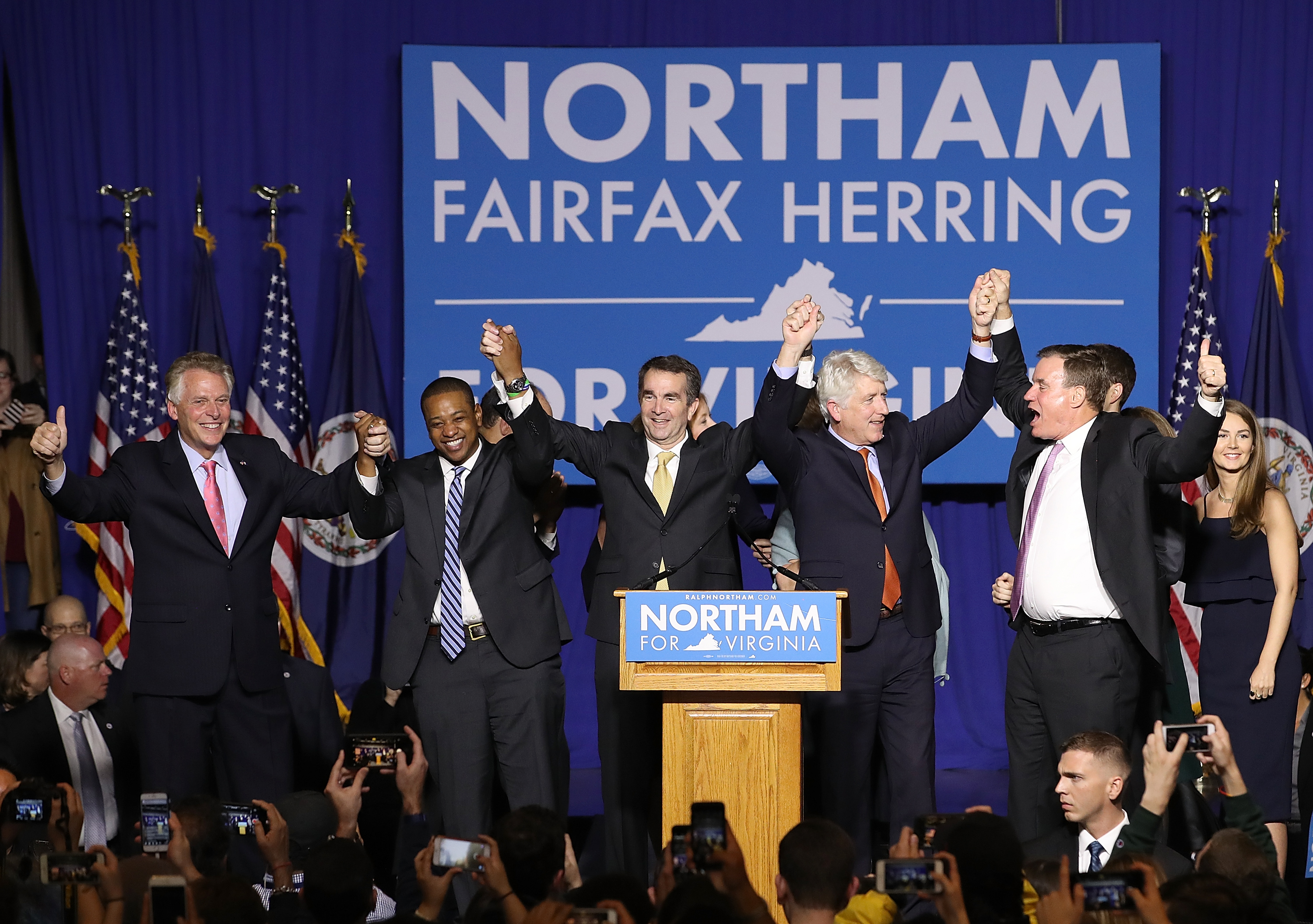 Gov.-elect Ralph Northam, center links arms with former Gov. Terry McAuliffe, Lt. Gov.-elect Justin Fairfax, Attorney General-elect Mark Herring, and U.S. Sen. Mark Warner (D-VA) at an election night rally November 7, 2017, in Fairfax, Virginia.