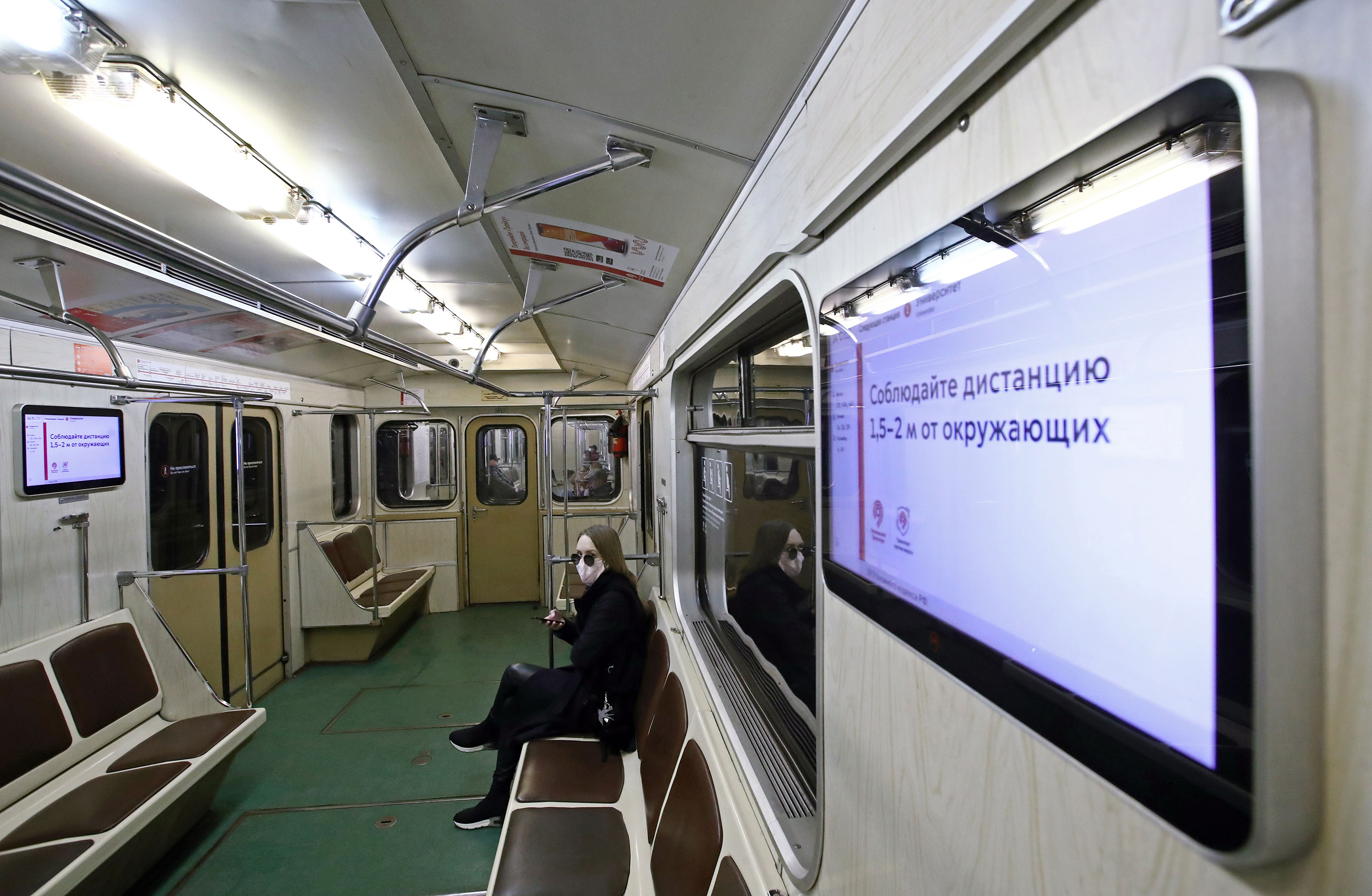 An announcement on a screen urges people to keep 1.5-2m apart in a subway car in Moscow on March 29.