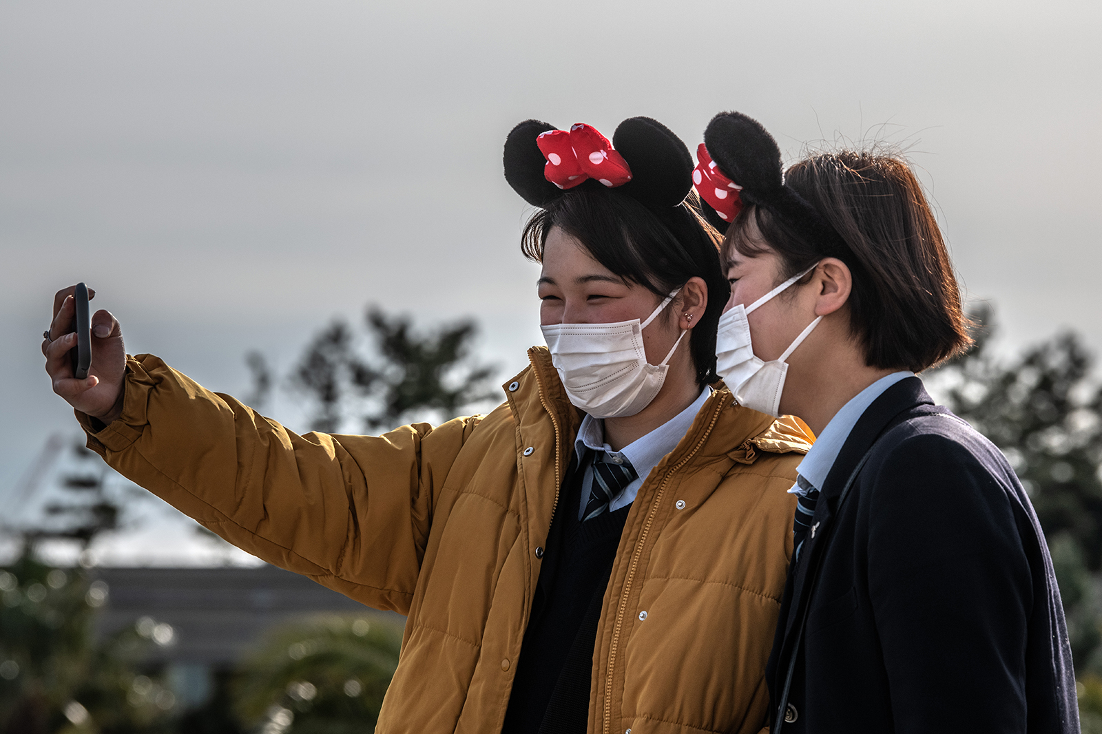 Girls wearing face masks and Disney-themed headbands take a selfie at Tokyo Disneyland on February 28, in Tokyo, Japan.