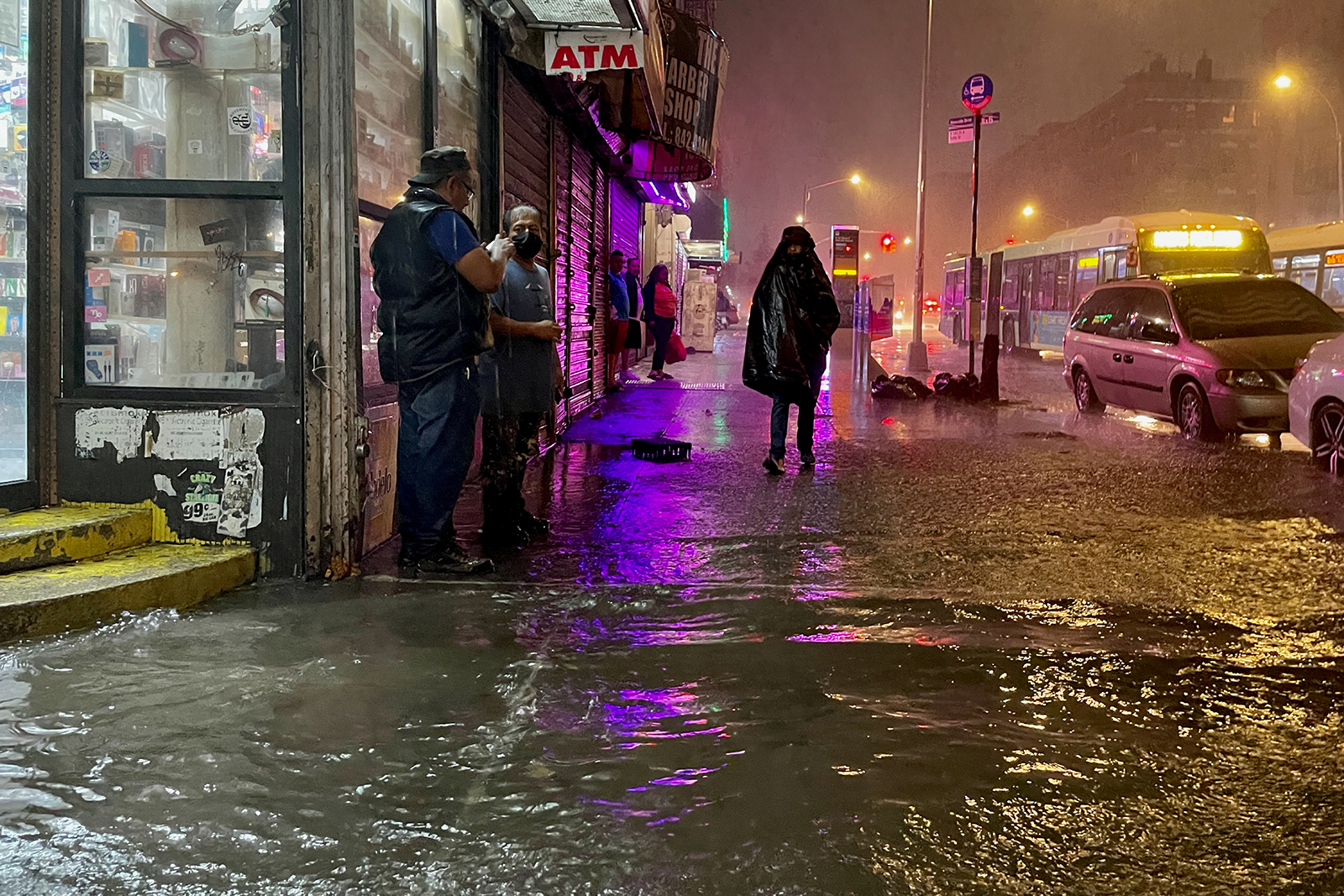 People make their way in rainfall from the remnants of Hurricane Ida on September 1, in the Bronx, New York City.