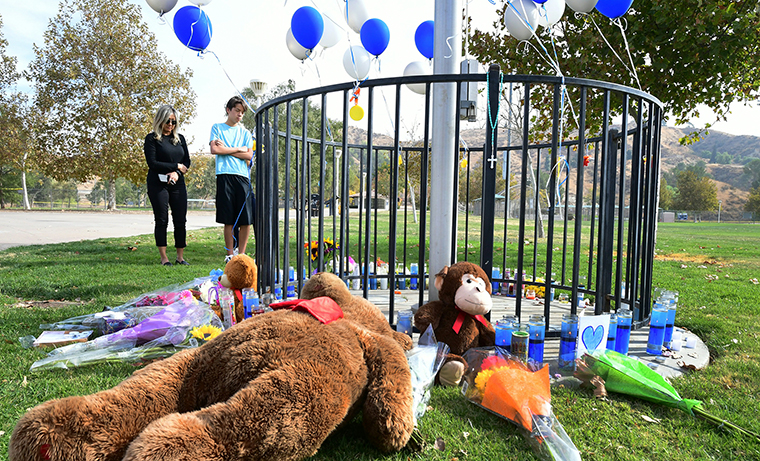 People grive beside a makeshift memorial in Central Park, not far from Saugus High School.