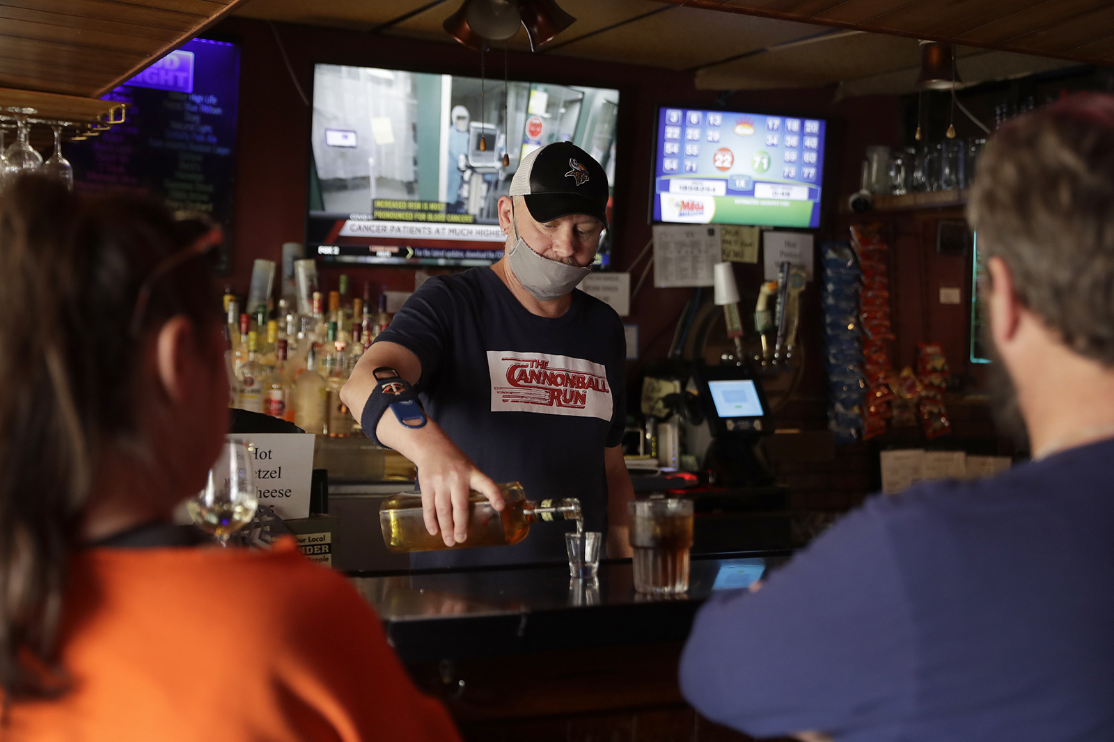 Bartender Greg Anderson pours drinks for customers in May, on the first day Tuner's Bar and Grill reopened in St. Charles, Missouri.