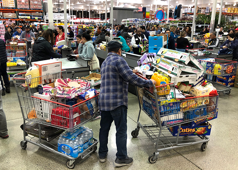 A Costco customer stands by his two shopping carts on Friday, March 13, in Richmond, California.