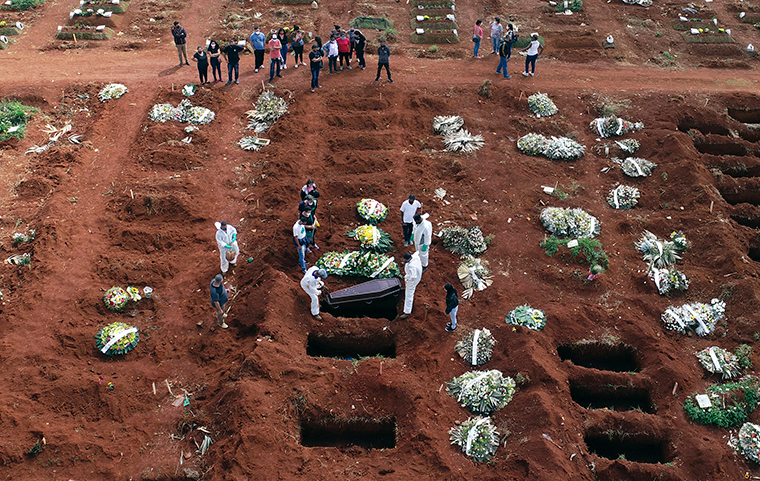 Cemetery workers wearing protective gear lower the coffin of a person who died from complications related to COVID-19 into a gravesite at the Vila Formosa cemetery in Sao Paulo, Brazil, Wednesday, April 7.
