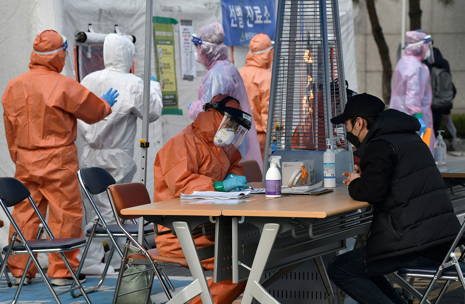 A medical staff member talks with a man with suspected symptoms of the COVID-19 coronavirus at a testing facility in Seoul on March 4.