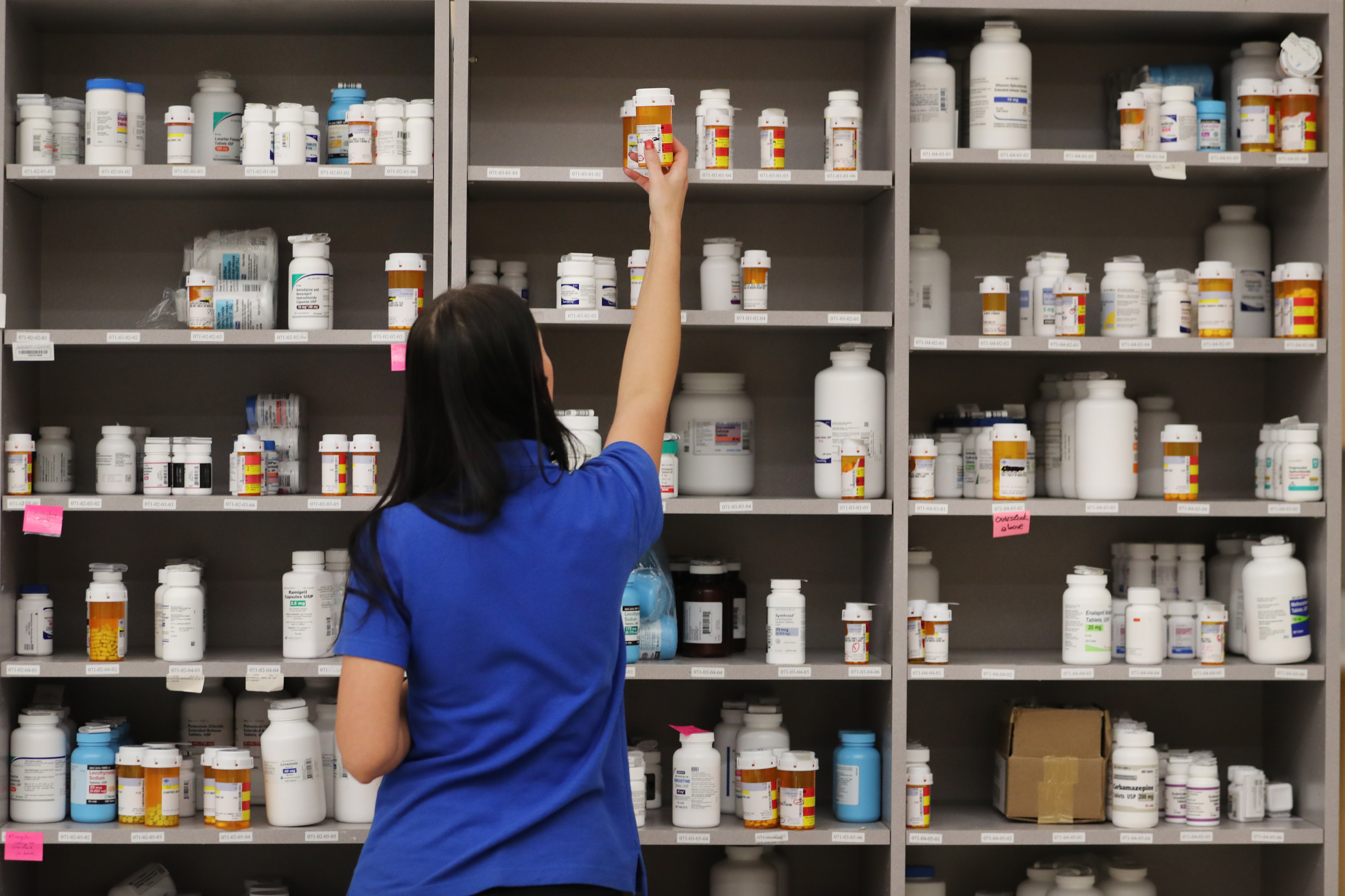 A pharmacy technician grabs a bottle of drugs off a shelve at a pharmacy in Utah.